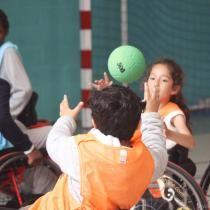 Des enfants pratiquent du handball en fauteuil roulant.