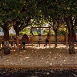 Des enfants jouent sur le mobilier en bois dans une cour d'école, à l'ombre des arbres.
