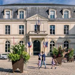 Façade de l'hôtel de Ville : des passants traversent la place, égayée par de grandes plantes.