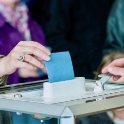 Un bulletin de vote est glissé dans une urne.