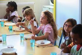 Enfants en train de manger leur dessert à la cantine.