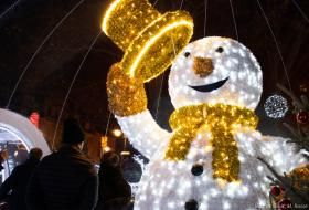 L'immense bonhomme de neige Sacha, tout illuminé, salue de son chapeau, devant le public tout petit.