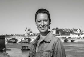 Portrait d'Agathe Gourdault-Montagne sur les bords de Loire, le pont Jacques-Gabriel et l'église Saint-Nicolas en arrière-plan.