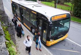 Un bus s'arrête pour laisser descendre plusieurs personnes.