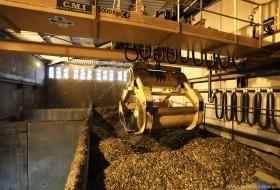 Intérieur de la chaufferie, où une pelle robotisée pioche dans un tas de bois déchiqueté.