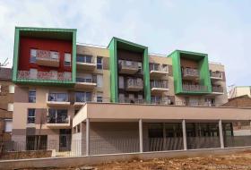 Façade arrière de la résidence, avec de grands rectangles, chacun différent, englobant des balcons.