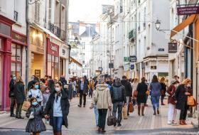 Nombreuses personnes masquées empruntant une rue commerçante.