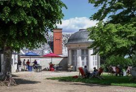 Des tables sont disposées pour se restaurer près du kiosque des jardins de l'évêché, sous les arbres.