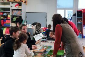 Des enfants jouent avec des adultes autour d'une table.
