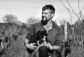 Portrait de William Théry avec son chien au milieu des vignes.