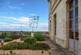 La sculpture est positionnée au milieu du jardin des aromatiques. L'Hôtel de Ville est à droite, la Loire en arrière-plan. Un enfant joue dans les allées.