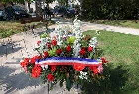 Gerbe de fleurs entourée d'un ruban bleu blanc rouge portant l'inscription : «Journée nationale de la déportation et 76e anniversaire de la libération des camps».