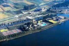 Photo aérienne du lac de Loire en 1983, avec des terrains de tennis, une piscine, un parking et d'autres nombreux aménagements en bord de Loire.