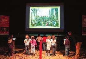 Des enfants observent un tableau projeté sur écran géant.