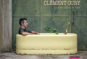 Visuel de l'album de Clément Oury, «La tête dans le mur» : le musicien est allongé dans une baignoire, dans une pièce semblant abandonnée.