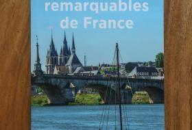 Couverture du nouveau guide Michelin «Sites & cités remarquables de France», figurant un bateau sur la Loire au premier plan, le pont Jacques-Gabriel avec sa flèche, et l'église Saint-Nicolas en arrière-plan.