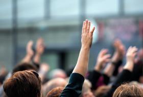 Mains levées parmi un groupe de personnes.