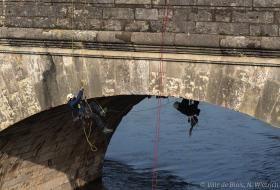 Des cordistes sont suspendus sous les voûtes du pont, pour y installer les nouveaux projecteurs.