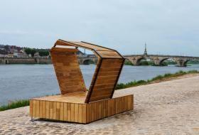 La promenade Mendès-France et ses pavés nouvellement aplatis, le long de la Loire avec le pont Jacques-Gabriel en arrière-plan. Au premier plan, un nouveau mobilier urbain en bois permet de s'assoir tout en étant abrité du soleil si besoin.