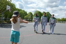 Une petite fille fait une passe à trois basketteurs de l'Ada sur un terrain en extérieur.