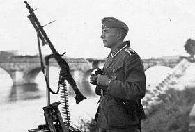 Un fantassin allemand en 1940 sur les rives blésoises de la Loire, aux côtés d'une mitrailleuse MG 34. En arrière plan, l'arche du pont Jacques-Gabriel, détruite le 18 juin.