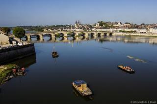 Fûtreaux sur la Loire, près du port de la Creusille, avec le Pont Jacques-Gabriel et l'église Saint-Nicolas en arrière-plan.