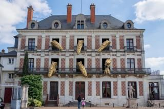 Six têtes de dragons automatisées sortent des fenêtres de la façade de la Maison de la magie.