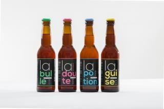 Quatre bouteilles de bière artisanale.