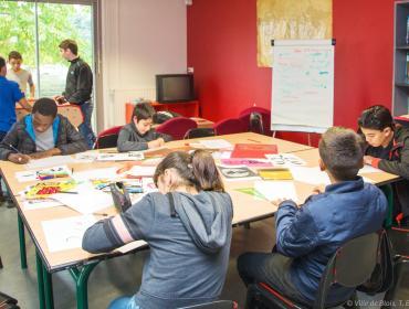 Des enfants dessinent sur une table et jouent au baby-foot, dans l'espace Jeunes Charcot.