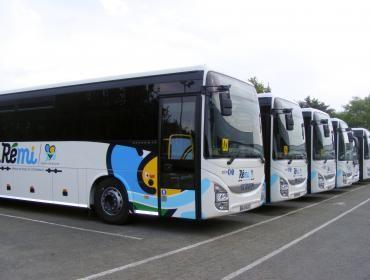 Cinq cars du réseau de mobilité interurbaine (Rémi) stationnés côte à côte.