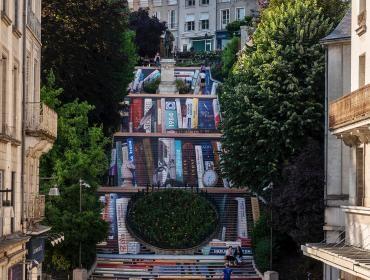 Photo d'ensemble de l'escalier, dont les contremarches sont décorées pour ensemble former l'illusion d'une bibliothèque géante, comportant une centaine de livres.