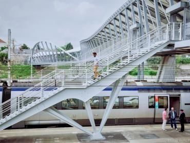 Deux usagers discutent avec un agent de la SNCF près d'un train à quai dans la gare.