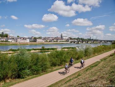 Trois cyclistes circulent sur la piste de la Loire à vélo et se dirigent vers le pont Jacques-Gabriel.