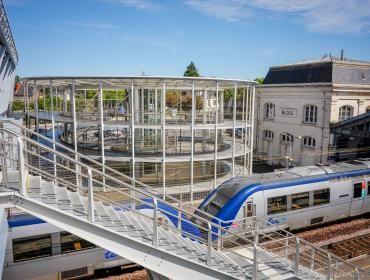 La passerelle, sa rotonde et les escaliers permettant d'accéder aux voies où un train est arrêté.