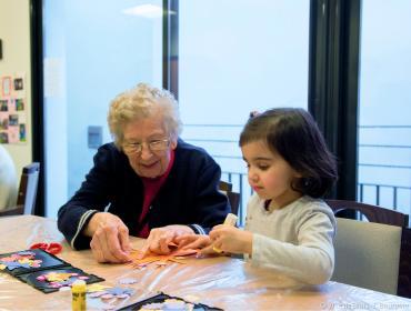 Une femme âgée et une jeune fille font de l'art plastique autour d'une table.