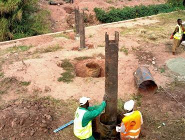 Des ouvriers enterrent des canalisations d'eau.