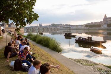 Des personnes sont assises sur les berges du port de la Creusille, face à la Loire.