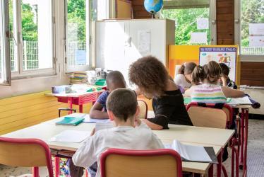 Une enseignante et deux enfants sont autour d'une table, en train de travailler.