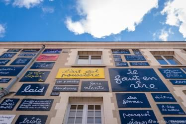 Des dizaines de tableaux-écritures de Ben accrochés à la façade de la Fondation du doute forment le Mur des mots.