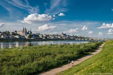 Deux coureurs longent les bords de Loire de Blois, entourés par la verdure.