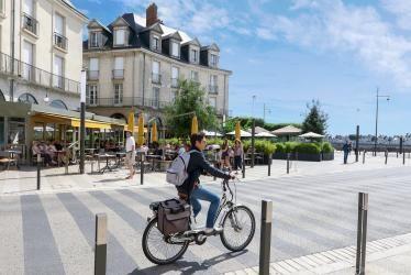 Une cycliste traverse la zone de rencontre de la place de la Résistance.