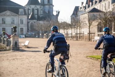 Deux personnes de la police municipale patrouillent à vélo dans les jardins de l'évêché.