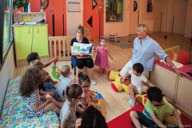 Des bambins sont réunis autour d'une assistante maternelle leur faisant la lecture.