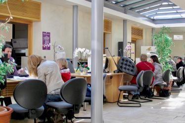 Des personnes assises face aux différents bureaux d'accueil du service Vie civile.