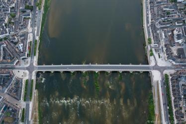 Photo aérienne prise au-dessus du pont Jacques-Gabriel, avec le quartier sud à gauche, le centre-ville à droite et la Loire au milieu.
