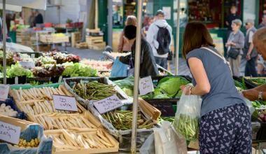 Une Blésoise se sert sur les étals de légumes d'un marché.