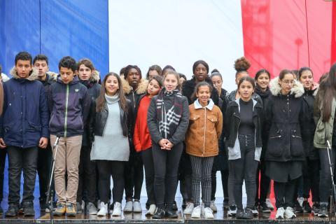 Des collégiennes et collégiens chantent la Marseillaise sur scène, avec un immense drapeau bleu-blanc-rouge en arrière-plan.