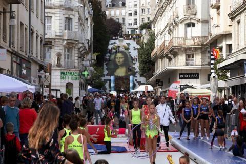 Des filles pratiquent la gymnastique dans la rue Denis-Papin entourées par la foule.