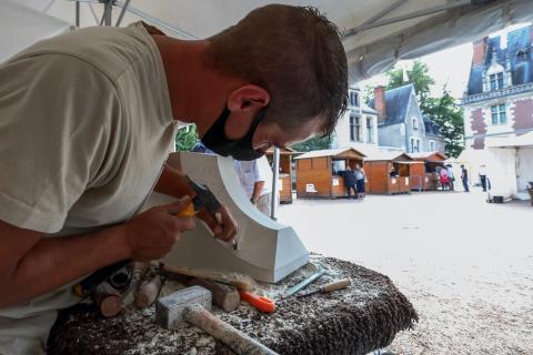 Un artisan tailleur de pierre de l'entreprise Lefèvre fait une démonstration sur la place du Château.