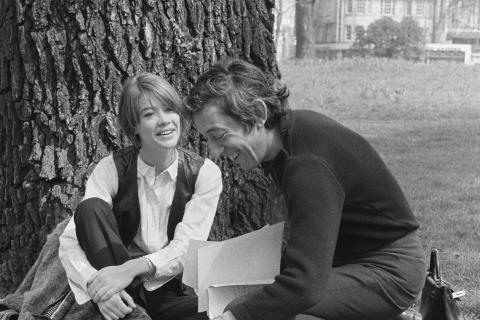 Portrait de Jane Birkin et Serge Gainsbourg dans un jardin. Elle, adossée à un arbre, lui parle et le regarde. Lui rigole, en rangeant des feuilles étalées par terre.